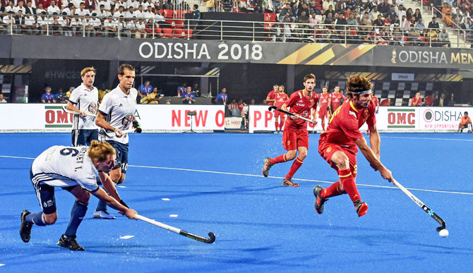A Spain player runs past France's Tom Genestet (6) during their Men's Hockey World Cup match in Bhubaneswar on Monday