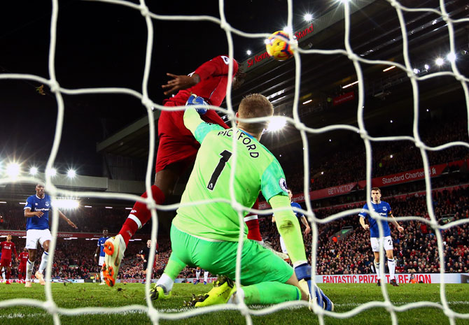 Divock Origi scores the winning goal for Liverpool past Everton goalkeeper Jordan Pickford