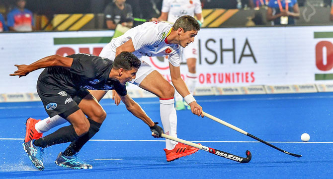 Spain's Xavi Lleonart (in white) and New Zealand's Arun Panchia vie for the ball, during their Men's Hockey World Cup matcj at Kalinga Stadium in Bhubaneswar on Thursday