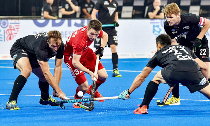 England's Zachary Wallace (red) is challenged by New Zealand players during their Men's Hockey World Cup match in Bhubaneswar on Monday