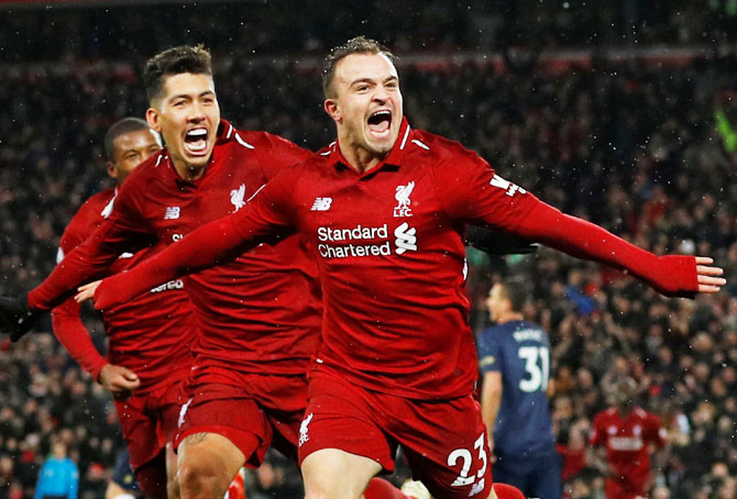 Liverpool's Xherdan Shaqiri celebrates with Roberto Firmino and Georginio Wijnaldum after scoring their third goal against Manchester United on Sunday