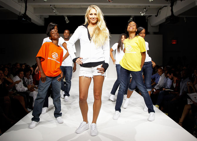 Tennis player Anna Kournikova walks the runway, donning K-Swiss 2009 fashion, with members of the Madison Boys and Girls Club during the 'Play Nice' runway show and party hosted by K-Swiss to kick off open week fever at Skyline Gallery in New York City on August 26, 2009