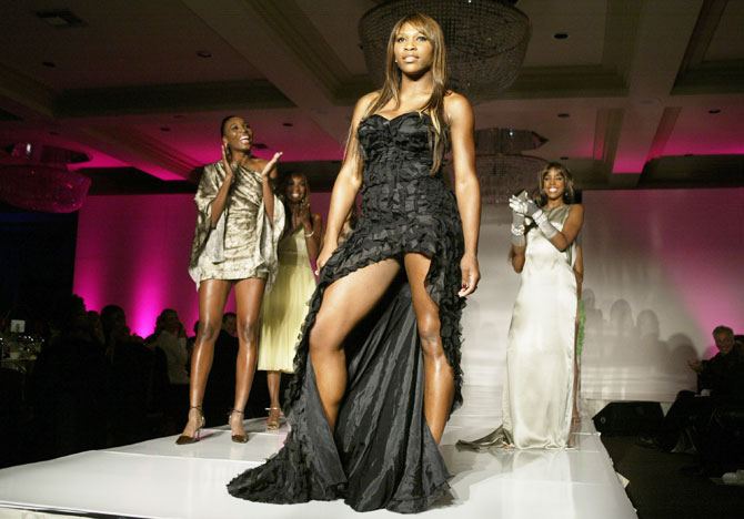 World tennis ace Serena Williams (centre) is applauded by her sister Venus (left) as she walks down the ramp during a fashion show displaying her 'Aneres' fashion line, during the WTA Tour Charities Show & Gala at the Fairmont Miramar Hotel in Santa Monica, California, on November 3, 2003