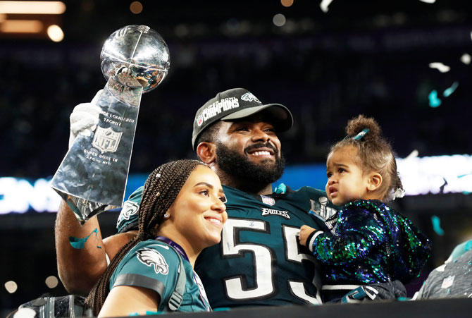 Philadelphia Eagles' Brandon Graham holds up the Vince Lombardi Trophy as he celebrates with his family after winning Super Bowl LII