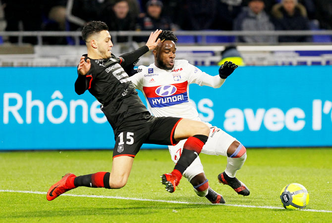 Lyon's Maxwel Cornet and Stade Rennes' Ramy Bensebaini vie for possession