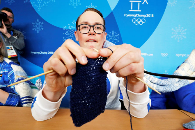Antti Koskinen, snowboard head coach, shows how he knits, during a news conference in Pyeongchang on Tuesday
