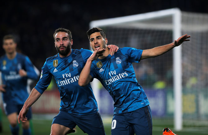 Real Madrid's Marco Asensio celebrates with teammate with Dani Carvajal after scoring their third goal against Real Betis in their La Liga at Estadio Benito Villamarin, Seville on Sunday
