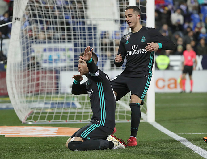 Real Madrid's Sergio Ramos celebrates with teammate Lucas Vazquez after scoring their third goal from the penalty spot against Leganes during their La Liga match at Butarque Municipal Stadium, in Leganes on Wednesday