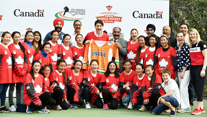 Canadian Prime Minister Justin Trudeau displays the Indian jersey as he poses for a photo with Indian women's ice hockey team in New Delhi on Saturday