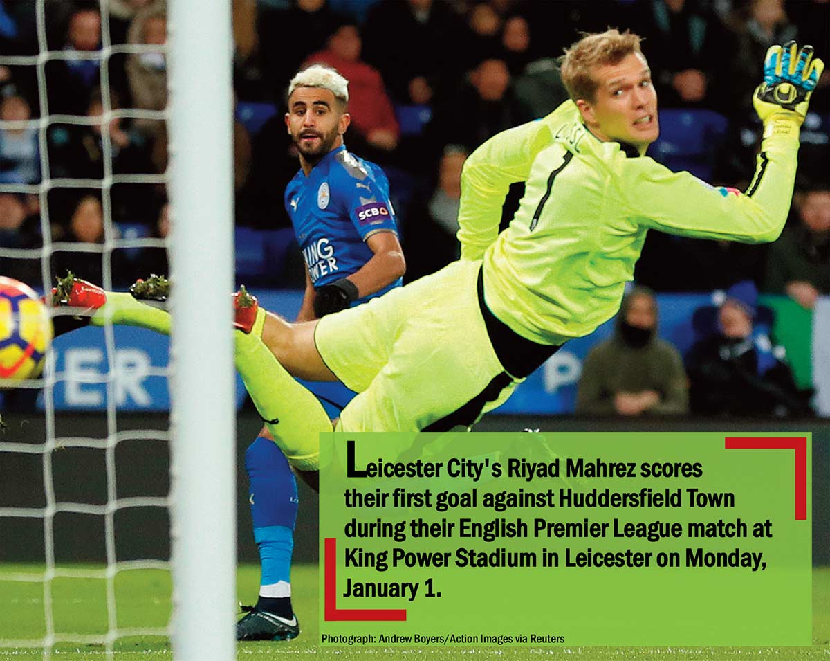 Leicester City's Riyad Mahrez scores their first goal against Huddersfield Town during their English Premier League match at King Power Stadium in Leicester on Monday, January 1