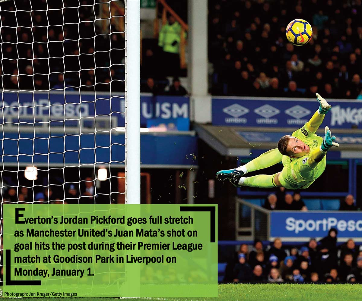Everton's Jordan Pickford goes full stretch as Manchester United's Juan Mata's shot on goal hits the post during their Premier League match at Goodison Park in Liverpool on Monday, January 1