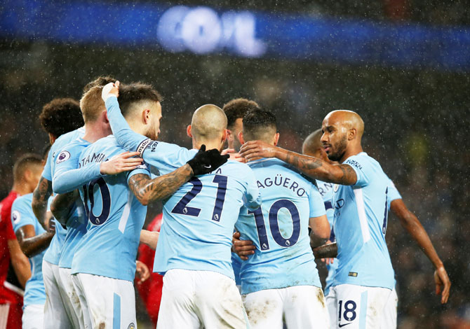 Manchester City's Sergio Aguero celebrates with teammates after scoring their third goal against Watford at the Etihad Stadium in London on Tuesday