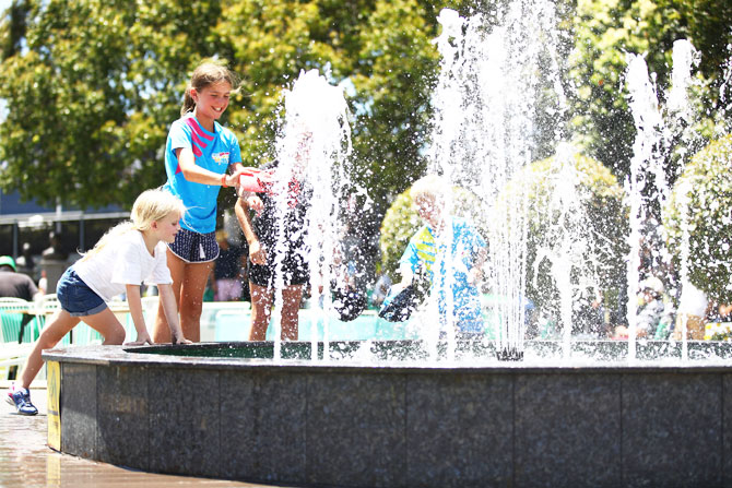 Young fans play in the fountain in Garden Square at Melbourne Park