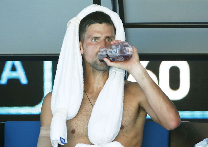Novak Djokovic has a drink during a break in his match against Gael Monfils