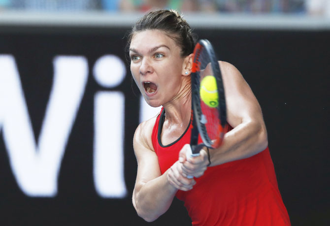 Romania's Simona Halep hits a return against Japan's Naomi Osaka