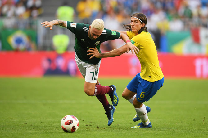 Mexico's Miguel Layun is tackled by Brazil's Filipe Luis