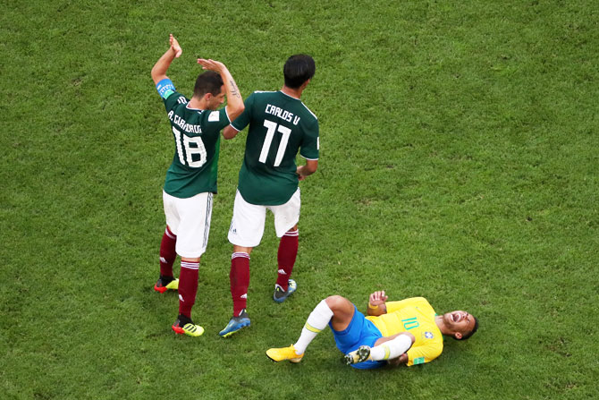 Neymar Jr of Brazil lies on the pitch injured while Andres Guardado and Carlos Vela of Mexico pass by