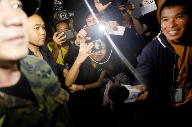 Journalists smile as they try to interview a military officer near the Tham Luang cave complex, as members of an under-16 soccer team and their coach have been found alive, according to a local media's report, in the northern province of Chiang Rai, Thailand on Monday