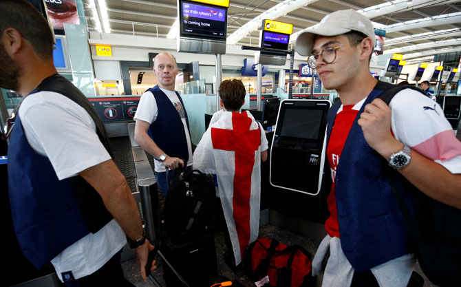 England football fans prepare to depart to Moscow for England's semi-final at the World Cup at Heathrow Airport in London on Tuesday