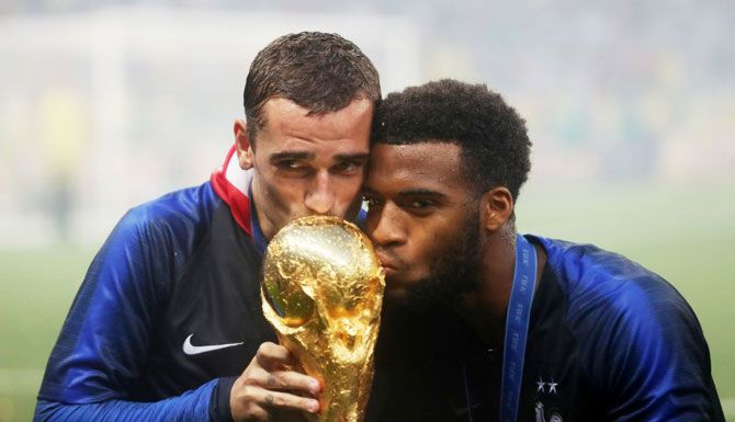 France's Antoine Griezmann and teammate Thomas Lemar kiss the trophy as they celebrate their World Cup win