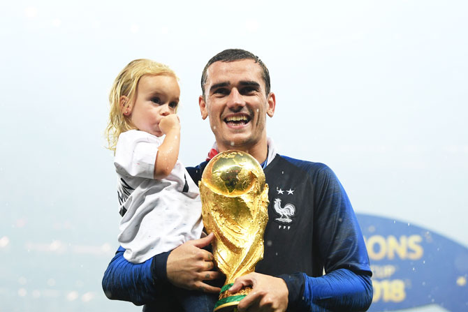 France's Antoine Griezmann celebrates victory with daughter Mia and the World Cup trophy