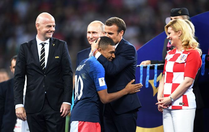 French President Emmanuel Macron awards Kylian Mbappe of France with the FIFA Young Player Award as President of Russia Vladimir Putin and President of Croatia, Kolinda Grabar Kitarovic look on following the 2018 FIFA World Cup final between France and Croatia at Luzhniki Stadium in Moscow, Russia, on Sunday