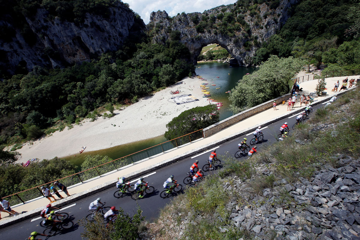 The peloton passes Vallon-Pont-d'Arc during the 188-km Stage 14 from Saint-Paul-Trois-Chateaux to Mende on July 21