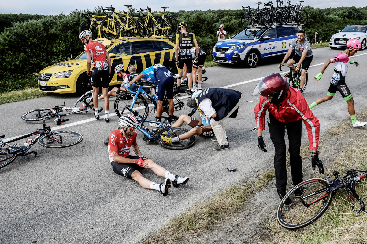 France's Axel Domont, Poland's Tomasz Marczynski, Belgium's Jelle Vanendert and Colombia's Daniel Martinez react after being caught in a massive pack fall in the last kilometers of the 195-km Stage 4 from La Baule to Sarzeau on July 10