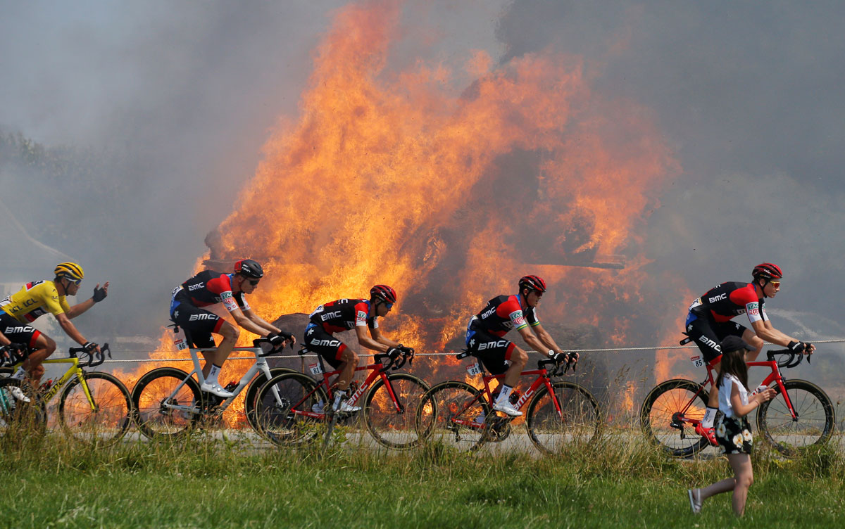 The peloton, with BMC Racing Team rider Greg Van Avermaet of Belgium in the overall leader's yellow jersey passes burning hay bales at the 181-km Stage 6 from Brest to Mur-de-Bretagne Guerleden on July 12