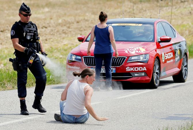 A police officer pepper sprays a protester as another protester stands in front of the race director's car during the 218-km Stage 16 from Carcassonne to Bagneres-de-Luchon on July 24