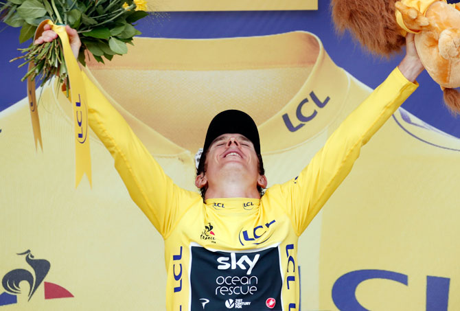 Team Sky rider Geraint Thomas of Britain celebrates on the podium, wearing the overall leader's yellow jersey on Saturday