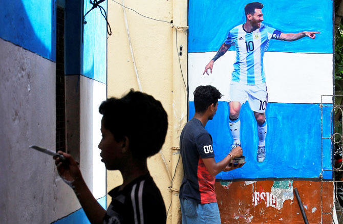 A boy paints a wall with the colours of Argentina's flag next to a man giving finishing touches to a cut-out of soccer player Lionel Messi after pasting it on a wall in an alley in Kolkata on June 10