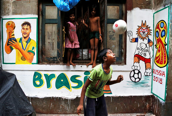 A boy plays in front an image of Brazil's Neymar painted on a wall in an alley at a slum in Kolkata on June 7