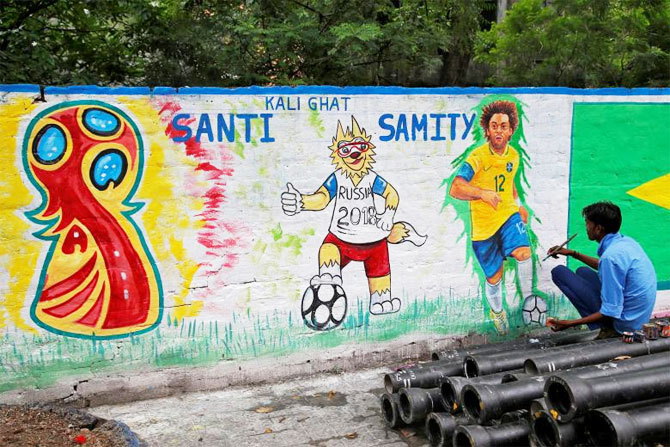 A painter applies finishing touches to an image of Brazil's Marcelo on a wall in Kolkata on June 4