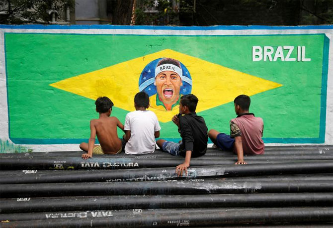 Boys sit on pipes in front of an image of Brazil's soccer player Neymar, painted on a wall, along a road, in Kolkata on June 4
