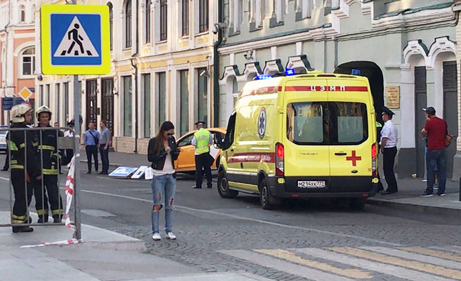 A damaged taxi, which ran into a crowd of people, is evacuated in central Moscow on Saturday