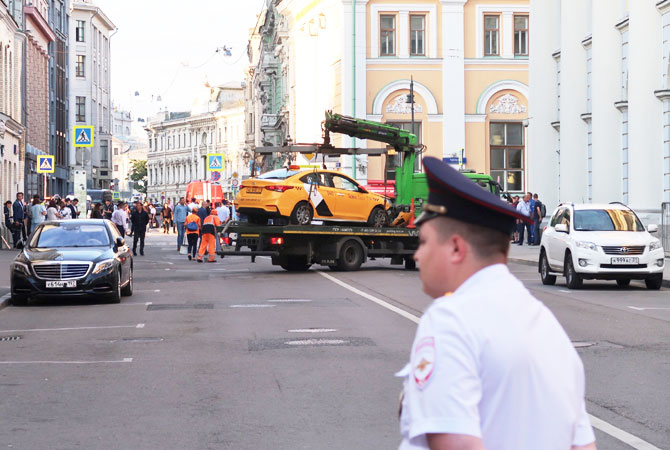 A damaged taxi, which ran into a crowd of people, is evacuated in central Moscow,