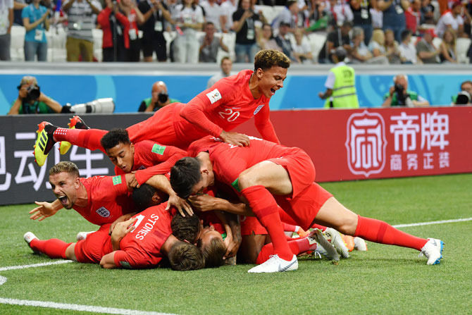 England captain Harry Kane celebrates with teammates after scoring the first goal against Tunisia