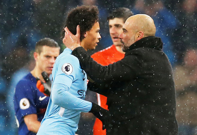 Manchester City manager Pep Guardiola celebrates with Leroy Sane after the match against Chelsea on Sunday
