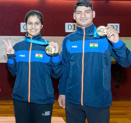 India's Manu Bhaker and Om Prakash Mitharval show off their medals after claiming the 10m air pistol mixed team title