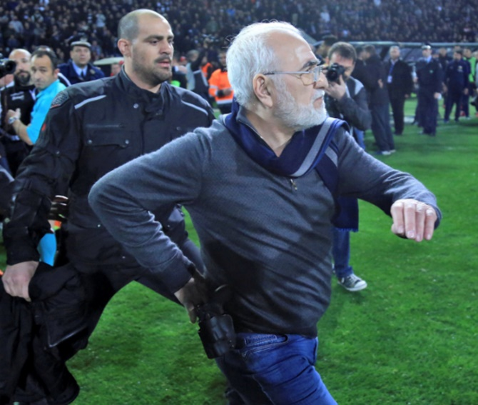 Russian-born Greek businessman and owner of PAOK Salonika, Ivan Savvides, centre, pictured with what appears to be a gun in a holster, enters the pitch after the referee annulled a goal of PAOK during their soccer match against AEK Athens on March 12
