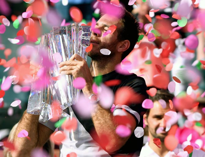 Juan Martin Del Potro poses with the trophy after defeating Roger Federer to win the Indian Wells tennis tournament on March 18