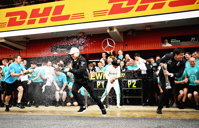 Mercedes GP drivers Lewis Hamilton and second place finisher Valtteri Bottas are drenched in champagne by their team members after the Spanish Formula One Grand Prix