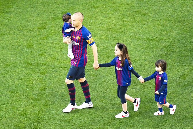 FC Barcelona's Andres Iniesta walks on the pitch with his daughters Valeria Iniesta and Siena Iniesta and his son Paolo Andrea Iniesta prior to the La Liga match between Barcelona and Real Sociedad at Camp Nou in Barcelona on Sunday