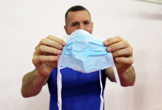 Swedish boxing coach Daniel Nash displays a medical face mask that was provided by a hotel staff on Monday