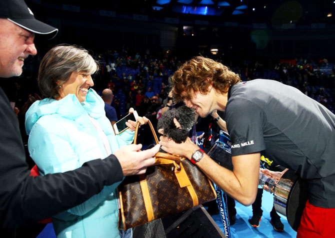 Alexander Zverev celebrates with his mum, Irina Zvereva and the family dog following his victory on Sunday