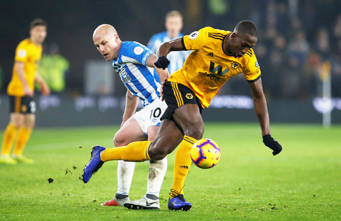 Wolverhampton Wanderers' Willy Boly and Huddersfield Town's Aaron Mooy vie for possession during their EPL match at Molineux Stadium on Wolverhampton on Sunday
