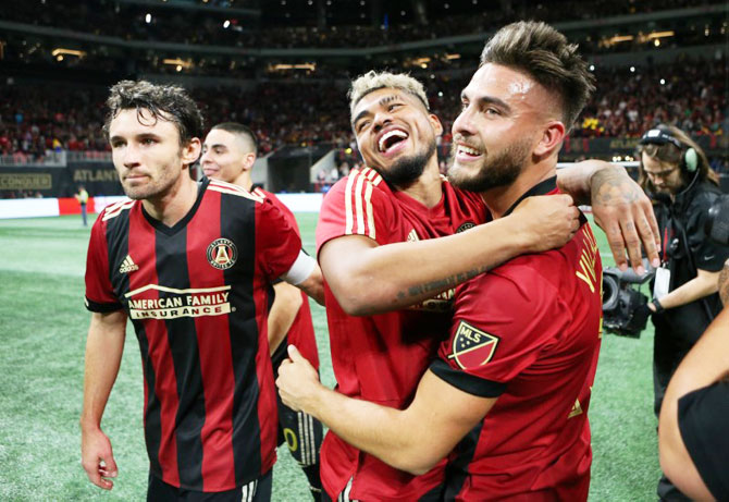 Atlanta United forward Josef Martinez (center) hugs teammate Hector Villalba (15) after the first leg of the MLS Eastern Conference Championship against the New York Red Bulls at Mercedes-Benz Stadium in Atlanta on Sunday
