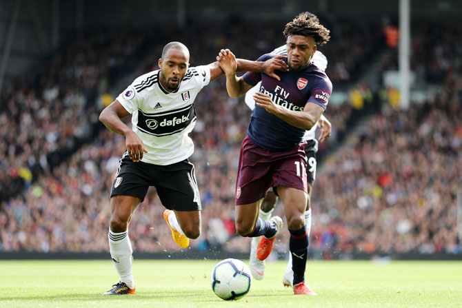 Arsenal's Alex Iwobi battles for possession with Fulham's Denis Odoi