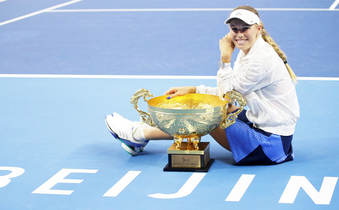 Denmark's Caroline Wozniacki celebrates with the trophy after winning the China Open women's singles final in Beijing, China, on Sunday